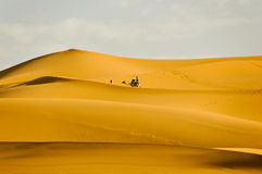 Tourist riding camel along sand dunes Stock Image