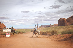 Tourist riding horse in Navajo Nation's Monument Valley Park. Royalty Free Stock Image