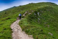 Ascent of a tourist. The tourist rises to the top of the mountains stock images