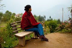 A tourist at Rishap hill top. A tourist is enjoying the natural beauty by seating on the bench of a tourist resort at hill top in Rishap, near Kalimpong at Stock Image
