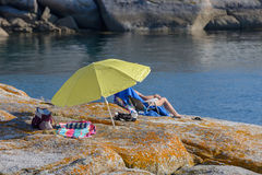 Tourist on a rocky beach under an umbrella Royalty Free Stock Images