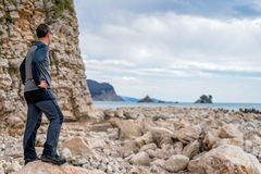 Tourist on the rocky coast in Montenegro. Single tourist standing on the rocky coast in Montenegro and admiring the beautiful landscape royalty free stock photo