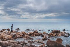 Tourist on the rocky coast in Montenegro. Single tourist standing on the rocky coast in Montenegro and admiring the beautiful landscape royalty free stock photos