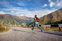 Tourist running on the road in mountains. Tourist woman with backpack and rainbow hat running down the asphalt road in the mountains near Big Almaty Lake in stock image