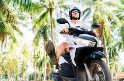 Tourist in safety helmet ride a motoroler under palm trees stock image