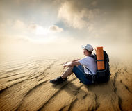 Tourist in sand desert. Tourist sitting in a sand desert and looking at sun Stock Image