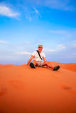 Tourist on a sand dunes. Tourist resting on top of the stunning sand dunes of Sahara desert in Merzouga, Morocco stock image