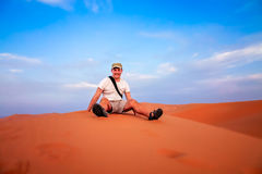 Tourist on a sand dunes. Tourist resting on top of the stunning sand dunes of Sahara desert in Merzouga, Morocco stock photos