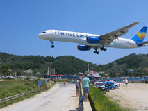 Landing of airplane on Skiathos over heads of people Royalty Free Stock Images