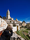 A tourist in Segovia. Nice view of Segovia, Spain. Typical houses, the Cathedral and a snowed hill as background Royalty Free Stock Images