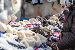 Tourist selects a warm slippers. In the market Royalty Free Stock Photos