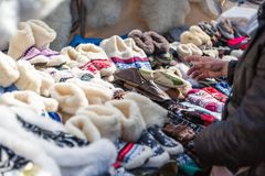 Tourist selects a warm slippers. In the market Royalty Free Stock Photo