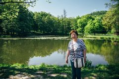Tourist senior beautiful woman in blue jeans and striped T-shirt standing on the bank of the mountain lake surrounded by forest,. Enjoying silence and harmony royalty free stock photo