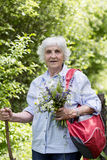 Tourist Senior woman with bouquet of flowers in the mountain Stock Photos
