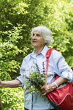 Tourist Senior woman with bouquet of flowers in the mountain Stock Photography