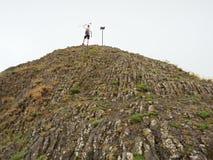 Tourist on sharp basalt  peak of volcano  formation Royalty Free Stock Photo
