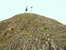 Tourist on sharp basalt  peak of volcano  formation Stock Images