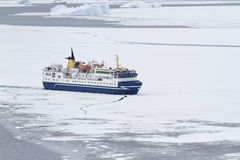 Tourist ship breaking ice in the strait of the Antarctic Peninsu Stock Images