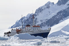 Tourist ship among the icebergs on the background of the mountai Stock Images