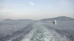A tourist ship leaves a wavy trail on the water. Beautiful view stock video footage