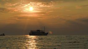 Tourist ship leaving pier at sunset stock video