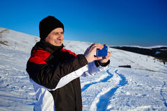Tourist shooting the landscape with mobile phone. Tourist shooting the beautiful winter landscape with his mobile phone Stock Image