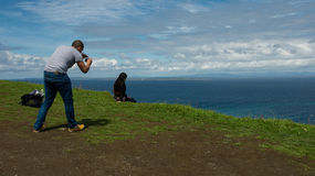 Tourist shooting a picture on the Cliff of Moher Stock Images