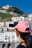Tourist shooting video. Woman tourist holding a camcorder filming her vacation in Amalfi, Italy Royalty Free Stock Photography