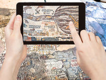 Tourist shoots photo ancient byzantine Madaba map. Travel concept - tourist shoots photo of ancient byzantine map of Holy Land, Madaba on smartphone, Jordan Royalty Free Stock Image