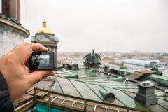 Tourist shoots video on action camera roof of St. Isaac`s Cathedral in St. Petersburg. Selective focus on hand with action camera Stock Images