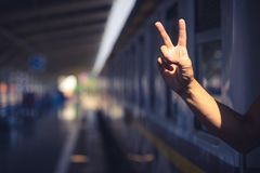 Tourist showing peace hand sign on the train stock photography