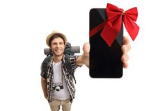 Tourist showing a phone wrapped with red ribbon as a gift Stock Photo