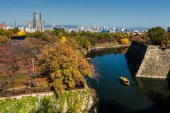 Torist boat at Osaka castle with autumn trees. Tourist or sightseeing boat sailing around Osaka castle canal with autumn foliage colors in Kansai, Japan stock photography
