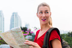 Tourist sightseeing with city map in Indonesia. Woman sightseeing city with touristic map in Jakarta, Indonesia royalty free stock images