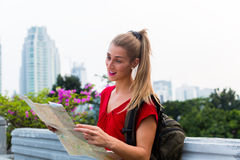 Tourist sightseeing with city map in Indonesia. Woman sightseeing city with touristic map in Jakarta, Indonesia royalty free stock photo