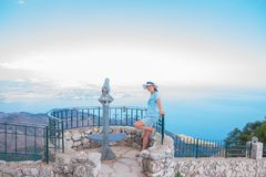 Tourist sightseeing coin operated telescope on the cliffs used for looking out into the sea.tourist Telescope and woman royalty free stock photo