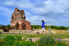 Tourist sightseeing old church ruins. Tourist woman sightseeing in the Red Church ruins in peaceful summer meadow nature,The Red church is the Early Medieval stock photos