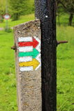 Tourist sign colorful arrows on the old wooden pole grounding. Red, green and yellow tourist track signs on the electric pole grounding Stock Image