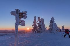 Tourist signpost mountain top Luzny covered by large ice. View of the snowy mountain peaks, view from Lusen in Bavaria in the morn Stock Photos