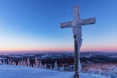 Tourist signpost mountain top Luzny covered by large ice. View of the snowy mountain peaks, view from Lusen in Bavaria in the morn Royalty Free Stock Image
