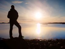 Tourist silhouette stand on beautiful rocky coastline above quiet ocean. Tall hiker enjoy Stock Image