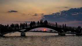 Tourist silhouettes stand on the bridge and gaze at the sunset. Levkas, greece Royalty Free Stock Image