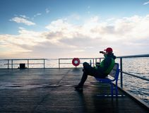 Tourist sit on bench on mole and take pohotos. Man enjoy morning at sea Royalty Free Stock Image