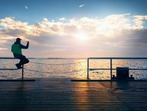 Tourist sit on mole handrail and takes pictures. Man enjoy morning at sea. Stock Images