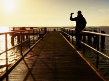 Tourist sit on mole handrail and takes pictures.Wooden boardwalk. Tourist sit on mole handrail and takes pictures. Man enjoy morning at sea. Wooden boardwalk royalty free stock photography