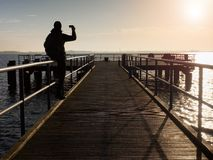 Tourist sit on mole handrail and takes pictures.Wooden boardwalk. Tourist sit on mole handrail and takes pictures. Man enjoy morning at sea. Wooden boardwalk stock photos