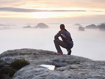 Tourist sit on peak of sandstone rock and watching into colorful mist and fog in  morning valley. Sad man Royalty Free Stock Photography