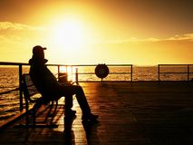 Tourist sit on wharf bench and enjoy misty sunny morning at sea. Smooth water Royalty Free Stock Photography