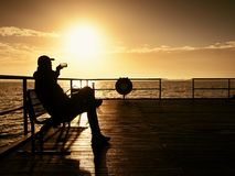 Tourist sit on wharf bench and enjoy misty sunny morning at sea. Smooth water Royalty Free Stock Image