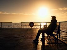 Tourist sit on wharf bench and enjoy misty sunny morning at sea. Smooth water Royalty Free Stock Photos